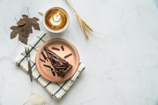 Gâteau au chocolat et café. gâteau au chocolat sur une plaque rose. gâteau sur fond de marbre blanc.