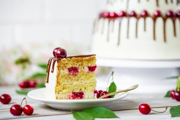 Gâteau au chocolat avec des cerises biologiques fraîches sur fond de bois rustique clair.