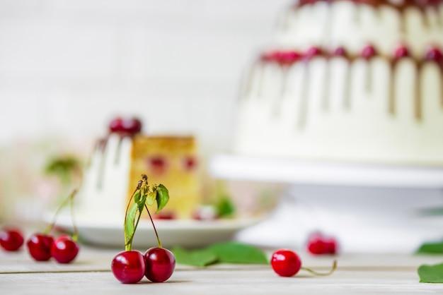 Gâteau au chocolat avec des cerises biologiques fraîches sur une surface en bois rustique légère.