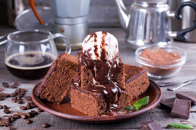 Gâteau au chocolat avec crème glacée et sauce au chocolat sur une assiette sur une table en bois