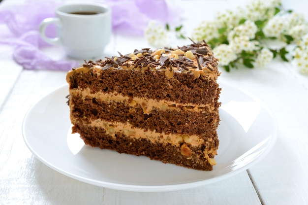 Gâteau au chocolat à la crème de noix sur une table en bois blanche. un morceau de gâteau sur une assiette et une tasse de café.