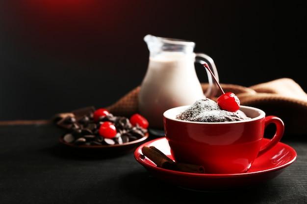 Gâteau au chocolat dans une tasse rouge avec une cerise sur fond noir