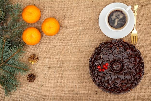 Gâteau au chocolat décoré de bouquet de viorne, tasse de café, oranges avec branche d'épinette sur table avec branche d'épinette, fourchette et sac.