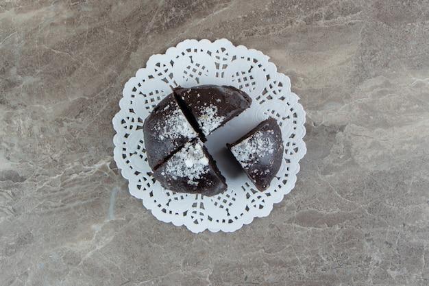 Gâteau au chocolat divisé en quatre morceaux sur une surface en marbre