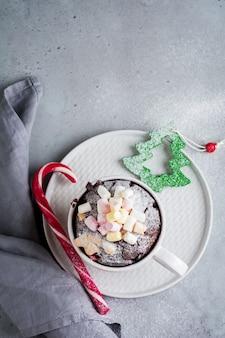 Gâteau au chocolat du nouvel an cuit au four à micro-ondes dans une tasse sur la texture de la surface grise vintage