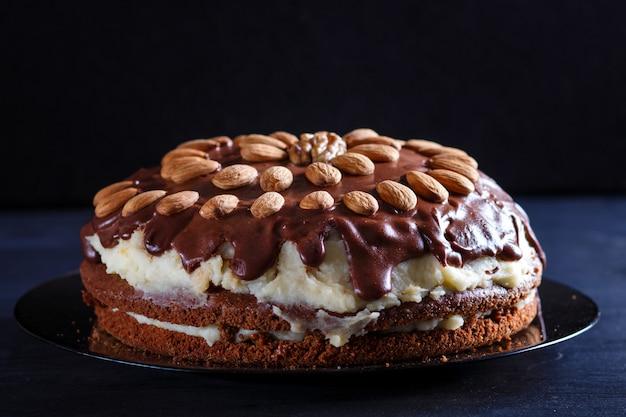 Gâteau au chocolat fait maison avec de la crème de lait et des amandes sur un fond en bois noir.
