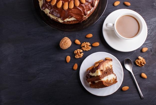 Gâteau au chocolat fait maison avec de la crème de lait, du caramel et des amandes sur une tasse de café noir.