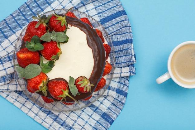 Gâteau au chocolat fait maison décoré de fraises fraîches et de feuilles de menthe sur plaque de verre avec serviette de cuisine et tasse de café sur fond bleu. vue de dessus
