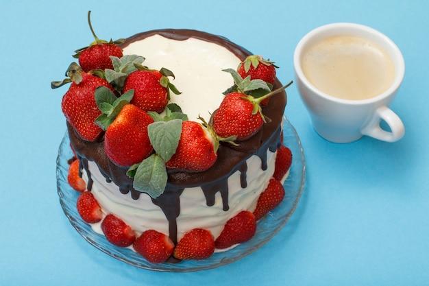 Gâteau au chocolat fait maison décoré de fraises fraîches et de feuilles de menthe sur plaque de verre et tasse de café sur fond bleu