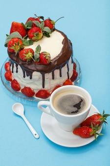 Gâteau au chocolat fait maison décoré de fraises fraîches et de feuilles de menthe sur plaque de verre et tasse de café avec soucoupe et cuillère sur fond bleu.