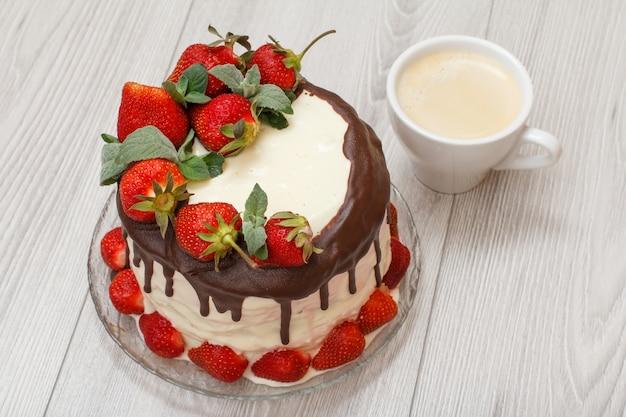 Gâteau au chocolat fait maison décoré de fraises fraîches sur plaque de verre et tasse de café sur fond de bois gris