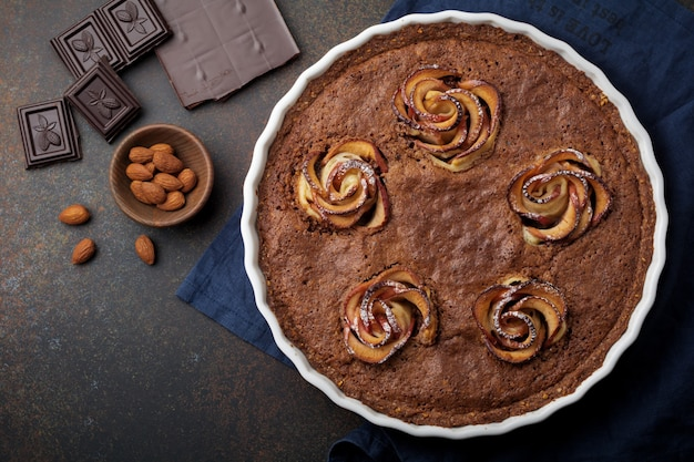 Gâteau au chocolat fait maison avec des fleurs de frangipane et de pommier sur un fond de béton foncé ou de pierre du bois. mise au point sélective. vue de dessus. copiez l'espace.