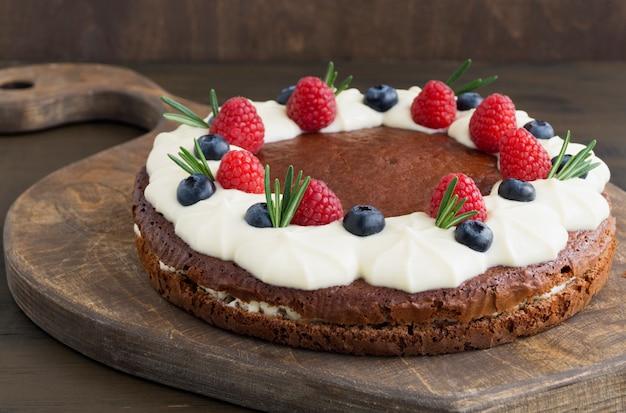 Gâteau au chocolat fait maison avec des framboises et des myrtilles.
