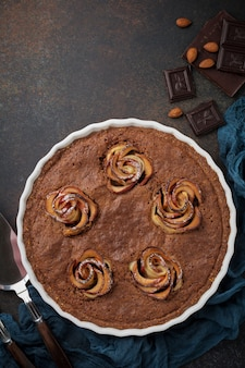 Gâteau au chocolat fait maison avec frangipane et fleurs de pommier sur un fond de béton foncé ou de pierre