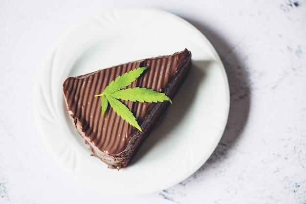 Gâteau au chocolat avec feuille de cannabis - plante de feuilles de marijuana sur plaque blanche, herbe nature nourriture cannabis