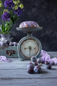 Gâteau au chocolat avec des fleurs lilas et des prunes dans une boîte en bois vintage