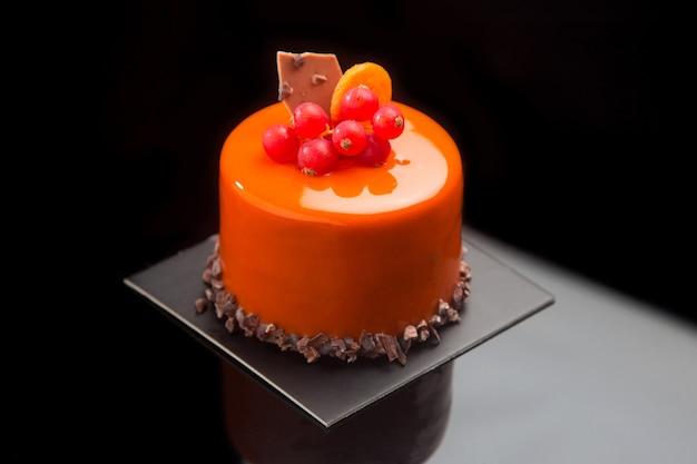 Gâteau au chocolat avec glaçage à l'orange et décoré de groseilles