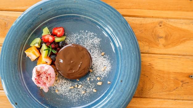 Gâteau au chocolat lave et crème glacée à la fraise sur une assiette bleue.