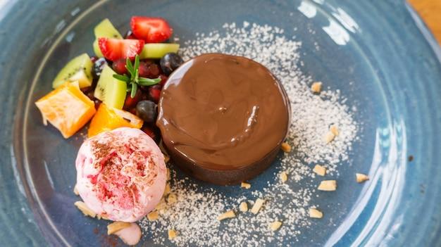 Gâteau au chocolat lave et glace à la fraise sur une assiette bleue.