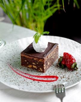 Gâteau au chocolat avec noix, crème glacée sur le dessus et fraises 1