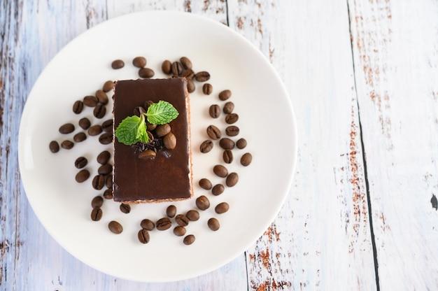 Gâteau au chocolat sur une plaque blanche avec des grains de café sur une table en bois