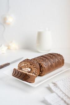 Gâteau au chocolat ou roulade avec de la crème tranchée avec un couteau, une serviette en textile et un verre de lait