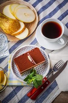 Gâteau au chocolat, une tasse de thé, citron et tranches de poire sur fond, horizontal.