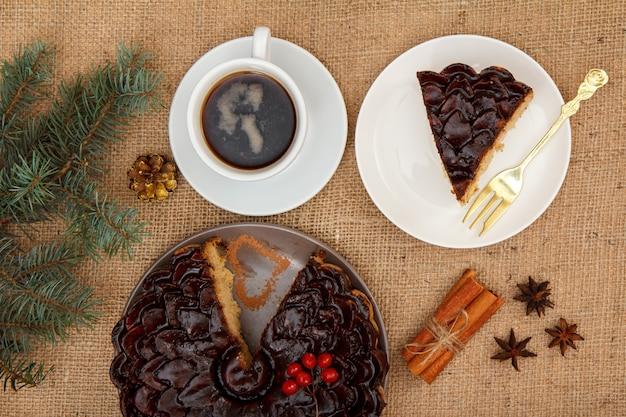 Gâteau au chocolat tranché décoré de bouquet de viorne, tasse de café, anis étoilé et cannelle sur table avec branche d'épinette et sac. vue de dessus