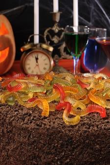 Gâteau au chocolat avec vers de gélatine sur la table de fête en l'honneur d'halloween
