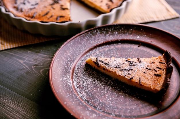 Gâteau au four sous forme de céramique saupoudré de tranches de chocolat sur une table en bois.
