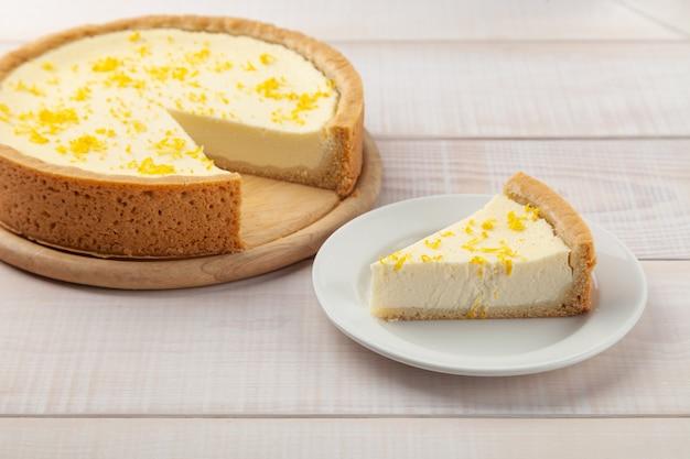 Gâteau au fromage au citron fait maison et morceau de tarte près de l'assiette