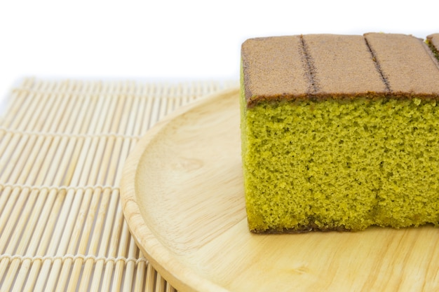 Gâteau au fromage au thé vert japonais matcha sur une assiette en bois et un tapis traditionnel