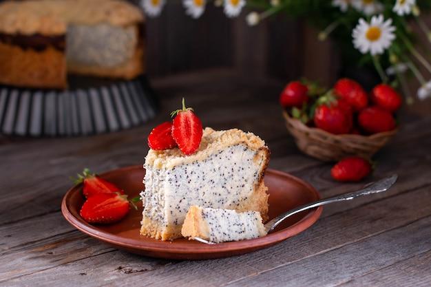 Gâteau au fromage aux graines de pavot fait maison dans une plaque en céramique sur un vieux fond en bois avec des fleurs et des fraises sur un fond