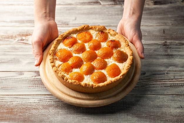 Gâteau au fromage aux pêches maison ronde dans les mains des femmes sur une plaque en bois, copiez l'espace, place pour le texte, vue d'en haut, gros plan