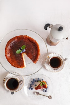 Gâteau au fromage brûlé basque fait maison sur une assiette avec des myrtilles et des feuilles de menthe sur une surface légère, avec flic de café et cafetière geyser vue de dessus à plat.