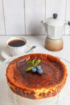 Gâteau au fromage brûlé basque maison sur une assiette avec des myrtilles et des feuilles de menthe sur une surface légère, avec une tasse de café et une cafetière geyser.