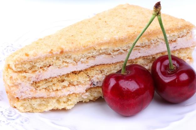 Gâteau au fromage avec une cerise sur un dessert sucré de fond blanc