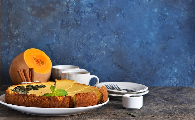 Gâteau au fromage à la citrouille classique fait maison sur un fond de béton bleu. mise au point horizontale.