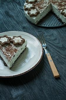Le gâteau au fromage cottage est décoré de biscuits et de chocolat noir râpé sur du bois foncé
