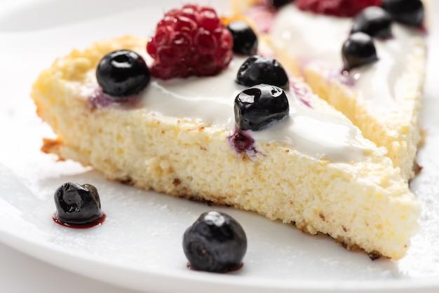 Gâteau au fromage avec de la crème et des framboises fraîches et des bleuets sur une plaque blanche