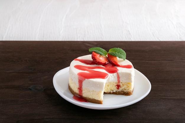 Gâteau au fromage double couche avec des fraises fraîches et du sirop de baies.