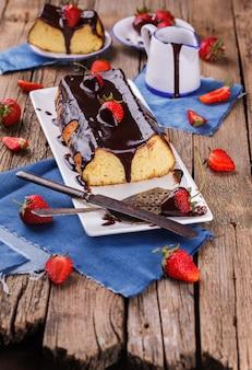 Gâteau au fromage avec du glaçage au chocolat et des fraises.