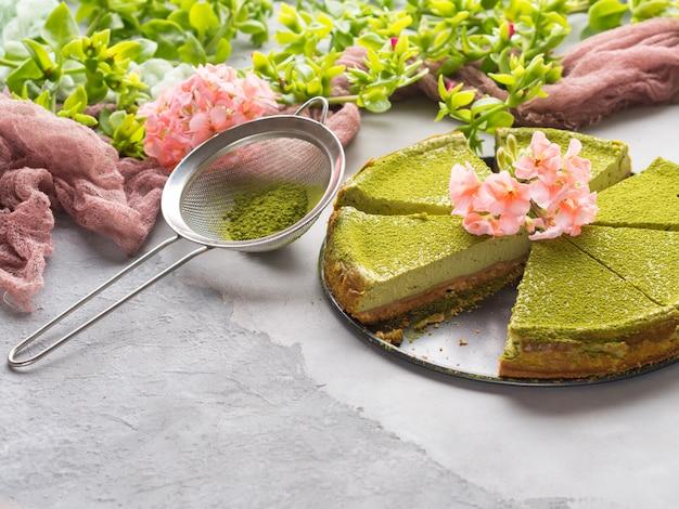 Gâteau au fromage matcha et fleurs roses sur béton gris