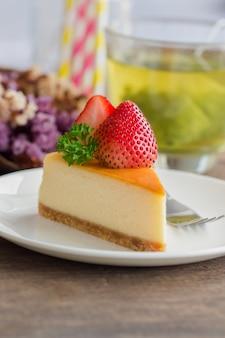 Gâteau au fromage new york fait maison sur une plaque blanche décorée de fraises et de persil frais