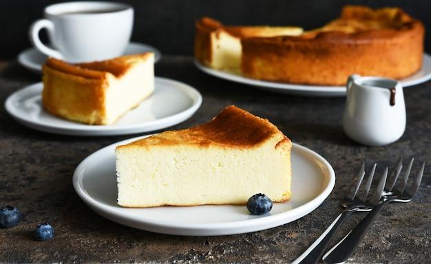 Gâteau au fromage new-yorkais. trancher le cheesecake et une tasse de café sur la table de la cuisine.