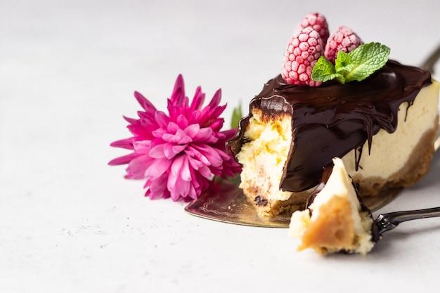 Gâteau au fromage à la new-yorkaise avec glaçage au chocolat, framboises et menthe. concept de la saint-valentin.