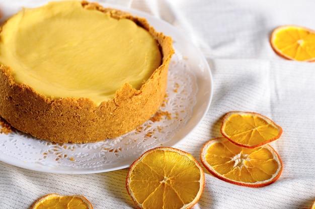 Gâteau au fromage à l'orange fait maison sur une nappe blanche près de tranches d'orange séchées
