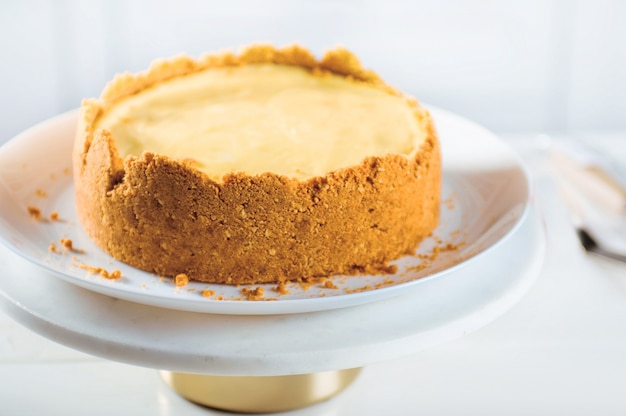 Gâteau au fromage à l'orange fait maison sur le stand sur une surface blanche