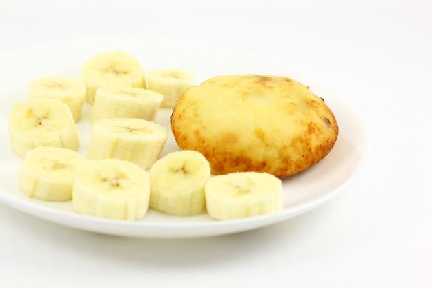 Gâteau au fromage ovale sur une plaque blanche avec des morceaux de banane en tranches