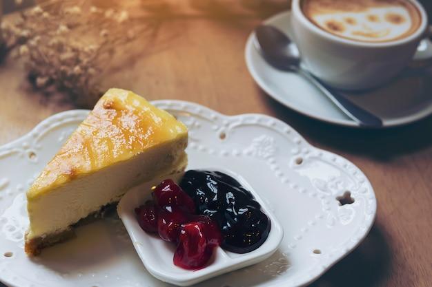 Gâteau au fromage avec une tasse de café chaud sur une table en bois